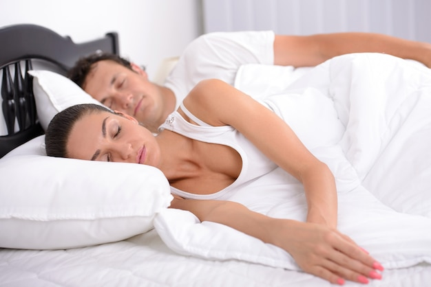 Premium Photo | Young adult couple sleeping on the bed in bedroom.