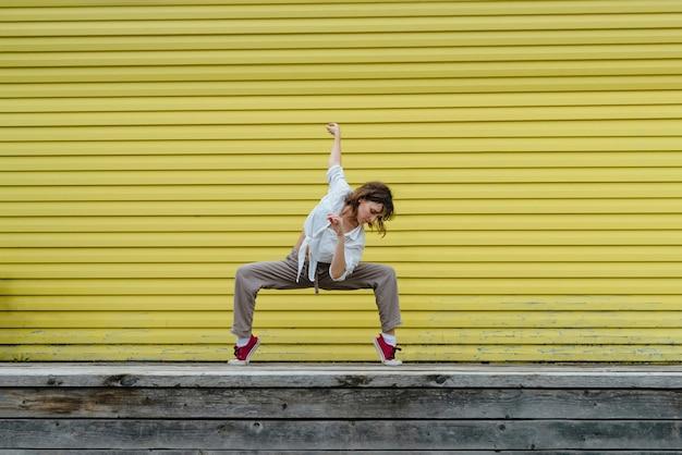 Молодая взрослая женщина в белой рубашке и серых льняных штанах танцует перед ярко-желтой стеной, выборочный фокус Premium Фотографии