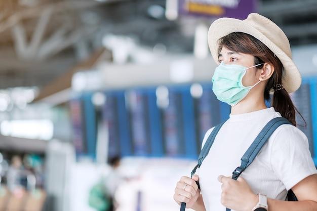 空港ターミナルでサージカルマスクを身に着けている若い成人女性、保護コロナウイルス病(covid-19)感染症、アジアの女性旅行者の帽子で旅行の準備ができています。新しいノーマルとトラベルバブルのコンセプト Premium写真