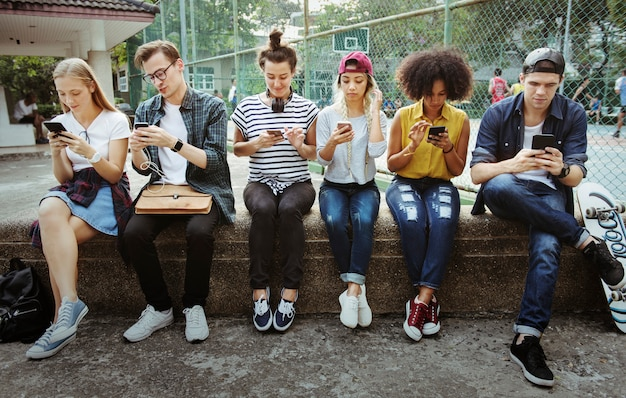 Young adult friends using smartphones together outdoors youth culture concept Premium Photo