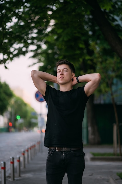 Young adult man in a black t-shirt and jeans walks on a city street on a sunny day Free Photo