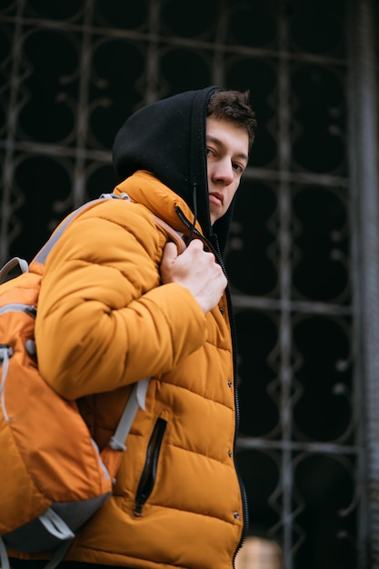 Young adult man in a yellow jacket walks on forged grate background. Free Photo