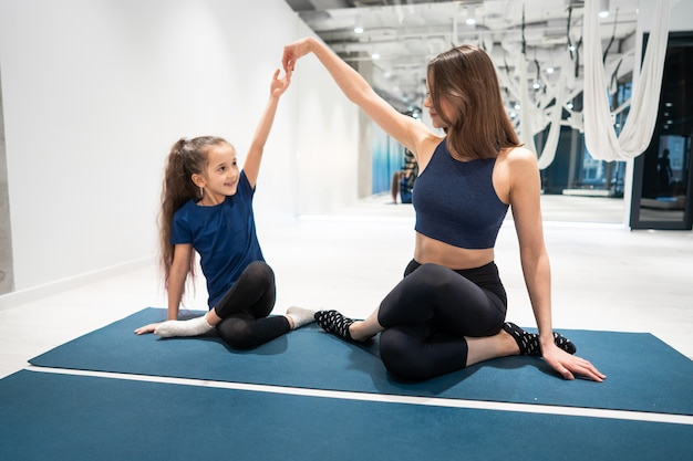 Young adult mom and little daughter together on aerobics Free Photo