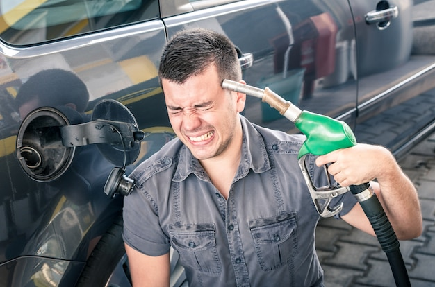 Young adult shooting himself over crazy petrol and fuel prices. Premium Photo