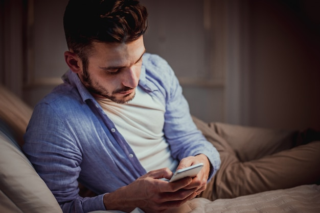 Young adult using smartphone at home Premium Photo