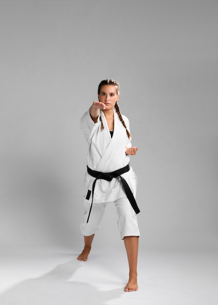 Young adult woman with black belt fighter training karate Free Photo