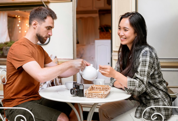 Giovane coppia avventurosa con una tazza di tè accanto al furgone Foto Gratuite