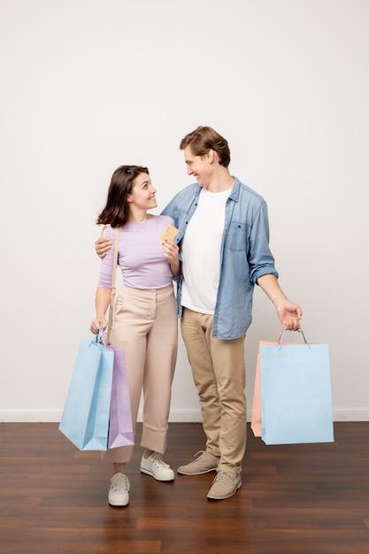 黒い金曜日に買い物に成功した後お互いを見てカジュアルウェアの愛情のこもったカップル Premium写真