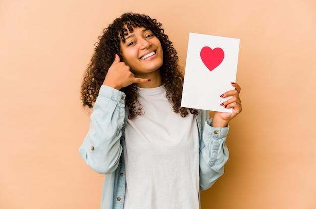 指で携帯電話の呼び出しジェスチャーを示すバレンタインデーカードを保持している若いアフリカ系アメリカ人のアフロ女性。 Premium写真
