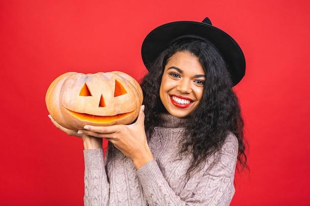 Молодая афро-американская черная женщина, держащая резную тыкву, изолированную на красном фоне Premium Фотографии