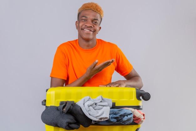 白い背景の上の側に彼の手の腕で指しているカメラの楽観的で陽気な笑顔を見て服の完全な旅行スーツケースとオレンジ色のtシャツを着ている若いアフリカ系アメリカ人の少年 無料写真