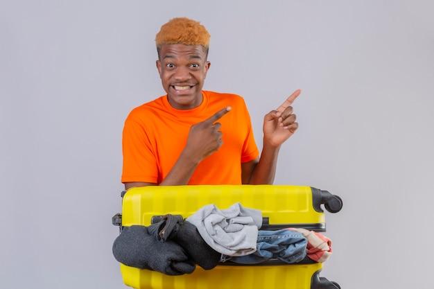白い背景の上の側に指で指で指しているカメラの楽観的で陽気な笑顔を見て服の完全な旅行スーツケースとオレンジ色のtシャツを着ている若いアフリカ系アメリカ人の少年 無料写真