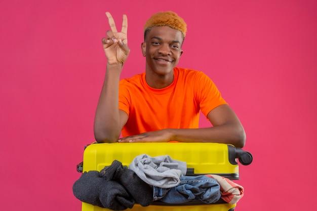 ピンクの背景に2番または勝利のサインを示すカメラの楽観的で陽気な笑顔を見て服の完全な旅行スーツケースとオレンジ色のtシャツを着ている若いアフリカ系アメリカ人の少年 無料写真