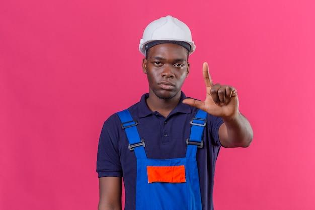 Молодой афро-американский строитель в строительной форме и защитном шлеме, стоящий с пальцем вверх, предупреждая об опасности на изолированном розовом Бесплатные Фотографии