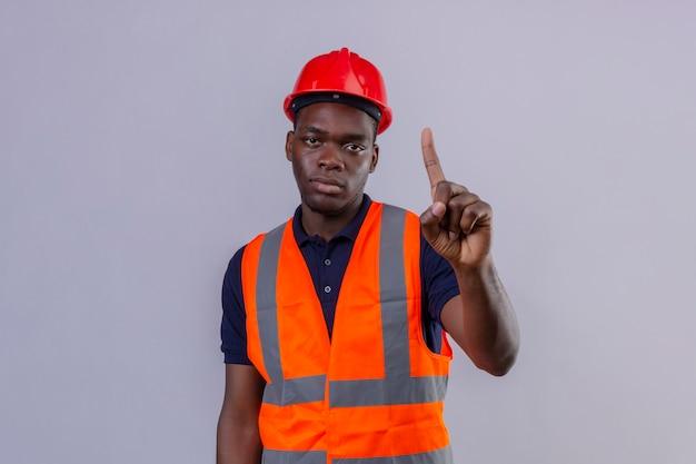 Молодой афро-американский строитель человек в строительном жилете и защитном шлеме, стоящий с пальцем вверх, предупреждая об опасности на изолированном белом Бесплатные Фотографии