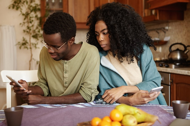Young african american couple using electronic gadgets at home: happy husband browsing newsfeed via social media while his jealous possessive wife spying, trying to see whose pictures he is liking Free Photo