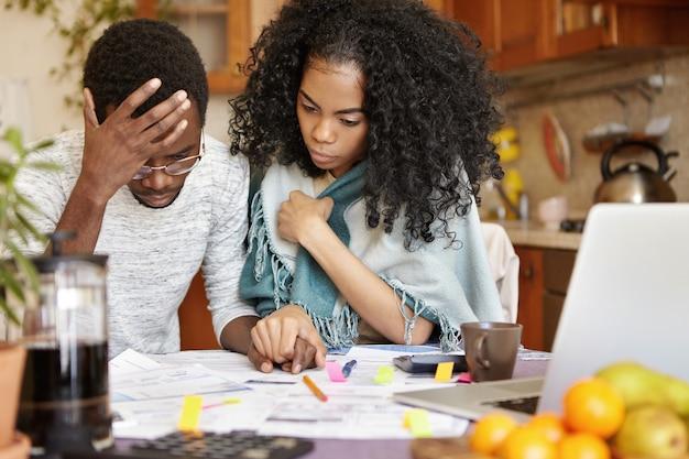 Giovane coppia afro-americana con molti debiti che calcolano le bollette del gas e dell'elettricità Foto Gratuite