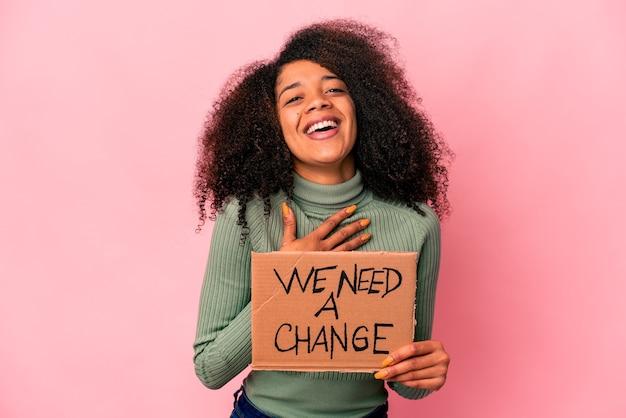 私たちが必要な変更を持っている若いアフリカ系アメリカ人の巻き毛の女性は、胸に手を置いて大声で笑います。 Premium写真