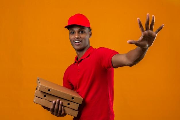 Молодой афро-американский работник доставляющий покупки на дом нося красную рубашку поло и крышку держа пакет салютуя с рукой с счастливым выражением над изолированным апельсином Бесплатные Фотографии