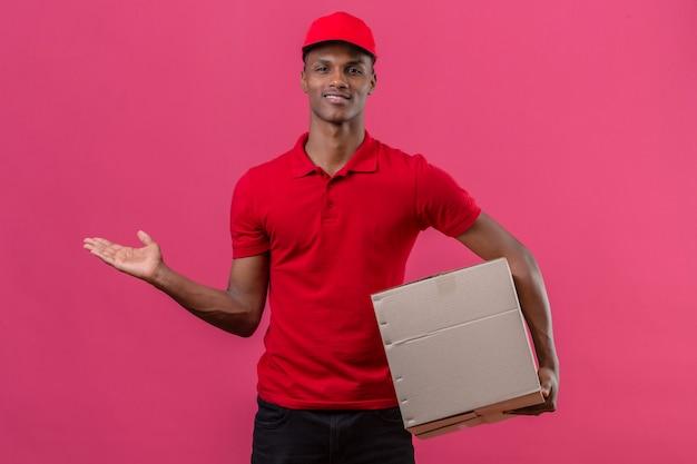 若いアフリカ系アメリカ人の配達人が赤いポロシャツを着て、段ボール箱を押しながら孤立したピンクの側に手を指している何かを提示 無料写真