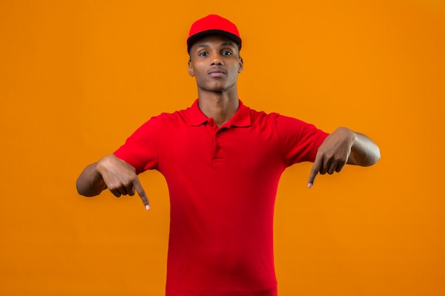 Young african american delivery man wearing red polo shirt and cap and pointing fingers down over isolated orange Free Photo