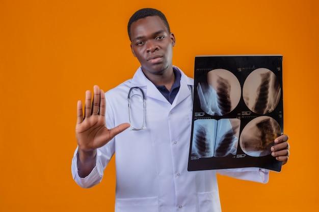 深刻な顔で開いた手で一時停止の標識を作る肺のx線を保持している聴診器で白衣を着ている若いアフリカ系アメリカ人医師 無料写真