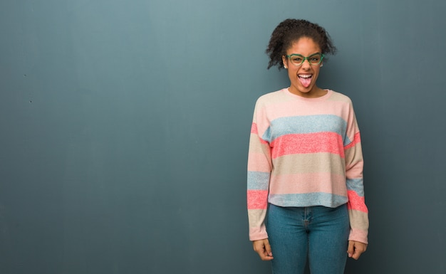 Young african american girl with blue eyes funnny and friendly showing tongue Premium Photo