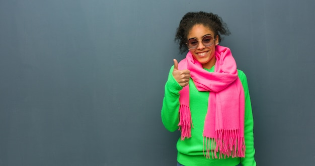 Young african american girl with blue eyes smiling and raising thumb up Premium Photo
