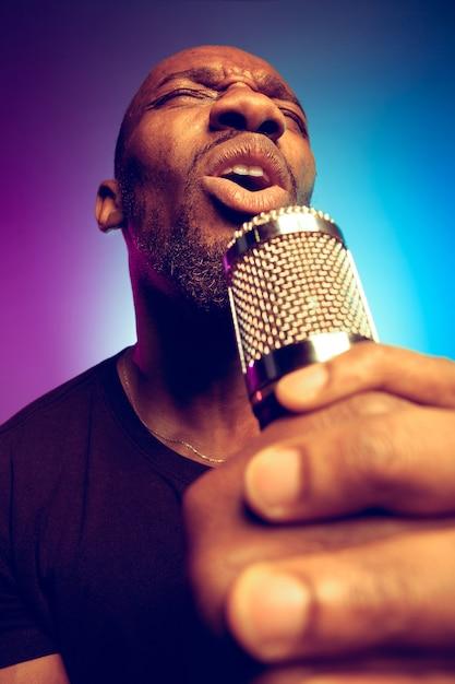 그라데이션 퍼플 블루에 노래를 부르는 젊은 아프리카 계 미국인 재즈 뮤지션 무료 사진