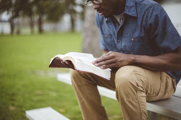 公園で座って聖書を読んでいる若いアフリカ系アメリカ人男性 無料写真