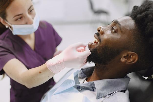 Giovane uomo afro-americano. ragazzo che visita l'ufficio del dentista per la prevenzione della cavità orale. uomo e medico di famiglia durante il controllo dei denti. Foto Gratuite