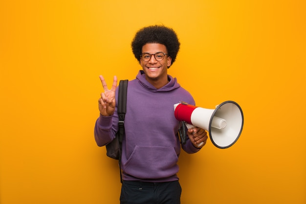 Young african american man holdinga a megaphone showing number two Premium Photo