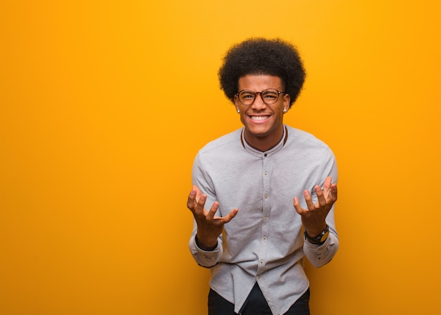 Young african american man over an orange wall angry and upset Premium Photo