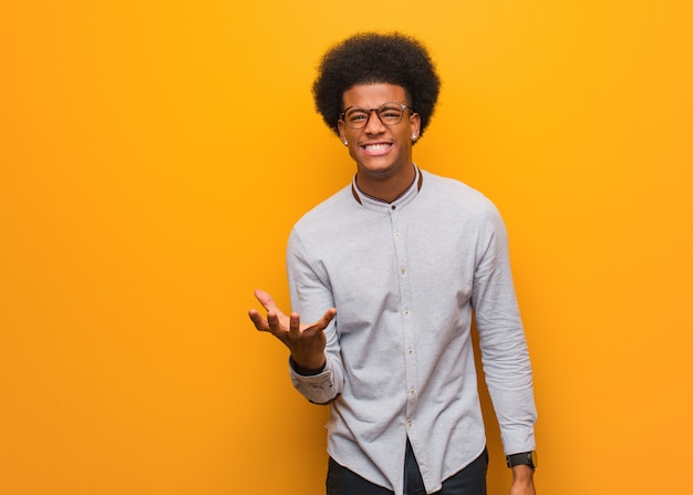 Young african american man over an orange wall very scared and afraid Premium Photo
