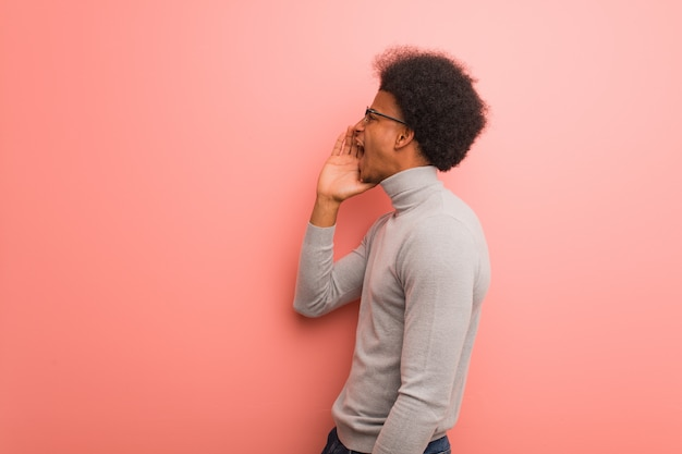 Young african american man over a pink wall whispering gossip undertone Premium Photo