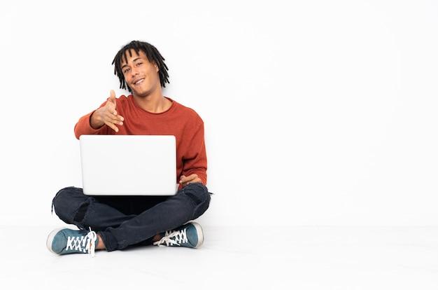 若いアフリカ系アメリカ人の男が床に座って、彼のラップトップを使って手を振って握手 Premium写真