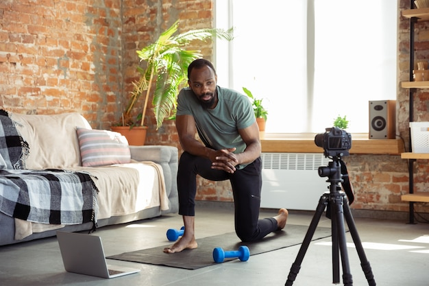 Young african-american man teaching at home online courses of fitness, aerobic, sporty lifestyle during quarantine, reording on camera, streaming Free Photo