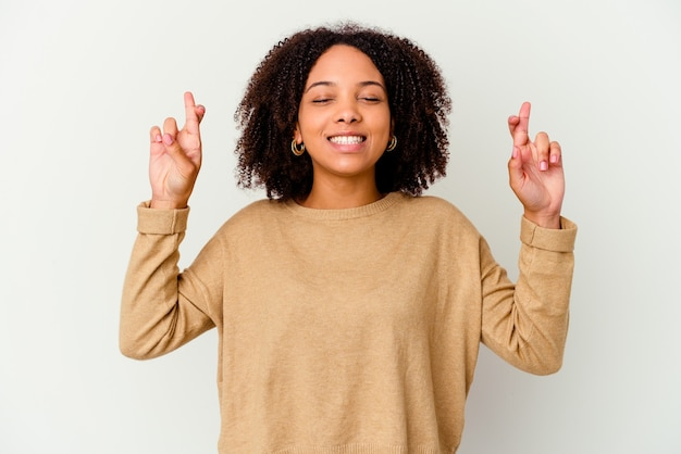 Молодая афро-американская женщина смешанной расы изолировала скрещивание пальцев за удачу Premium Фотографии