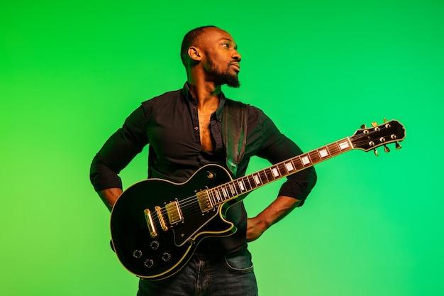 그라데이션 녹색 노란색에 록 스타처럼 기타를 연주하는 젊은 아프리카 계 미국인 음악가 무료 사진