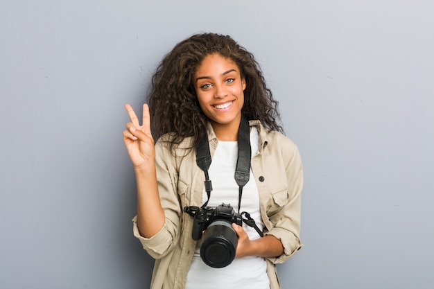 Young african american photographer woman holding a camera showing number two with fingers. Premium Photo