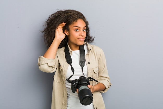 Young african american photographer woman holding a camera trying to listening a gossip. Premium Photo