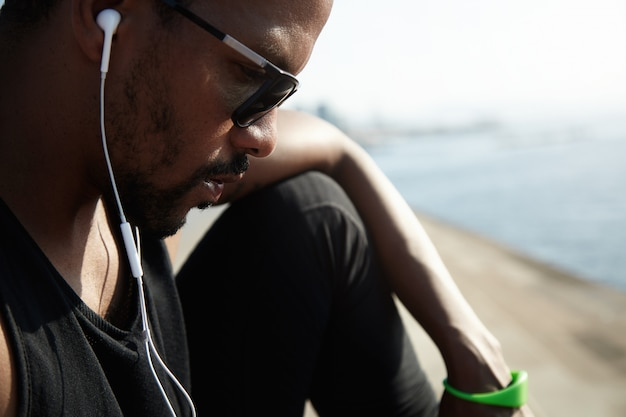 Young african american rapper in black top listening to new tracks outside under blue sky. handsome and serious man sitting alone on the roadside and chatting with his friends on his digital device. Free Photo