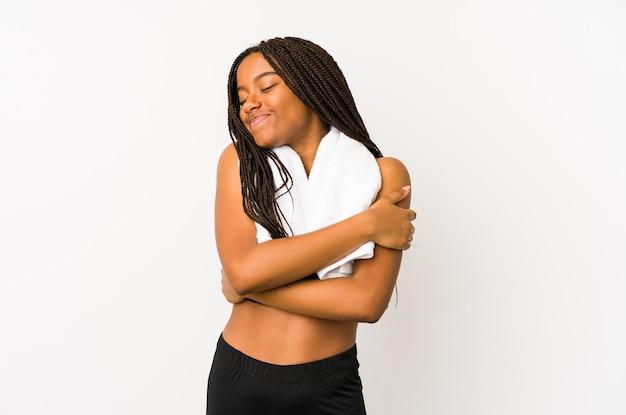 若いアフリカ系アメリカ人のスポーツの女性は抱擁、屈託のない、幸せな笑顔を分離しました。 Premium写真