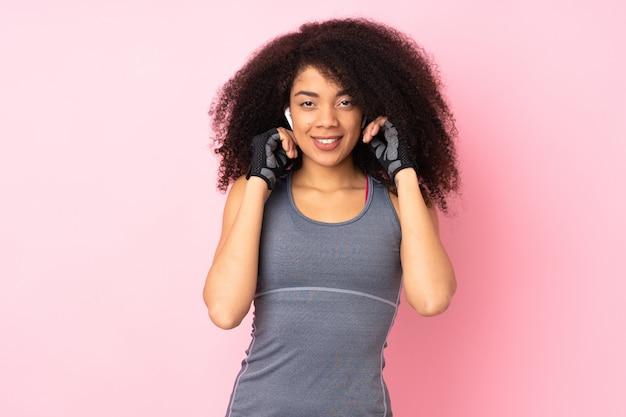 ピンクのリスニング音楽に分離された若いアフリカ系アメリカ人スポーツの女性 Premium写真