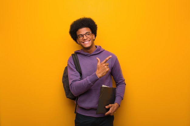 Young african american student man pointing to the side with finger Premium Photo