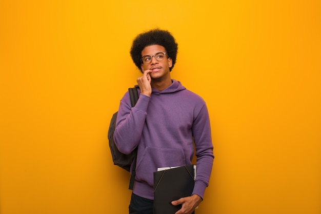 Young african american student man relaxed thinking about something looking at a copy space Premium Photo