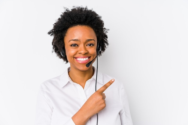 Young african american telemarketer woman isolated smiling and pointing aside, showing something at blank space. Premium Photo