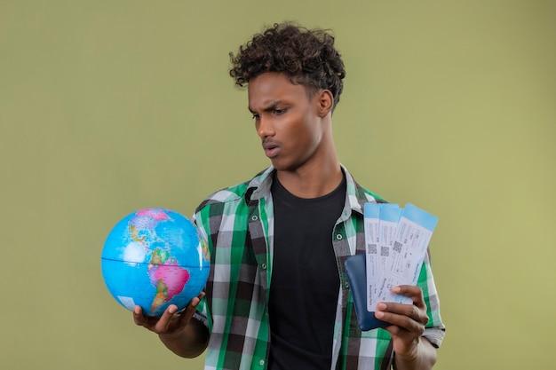 젊은 아프리카 계 미국인 여행자 남자 항공 티켓을 들고 얼굴에 심각한 표정으로보고, 찡그림 무료 사진