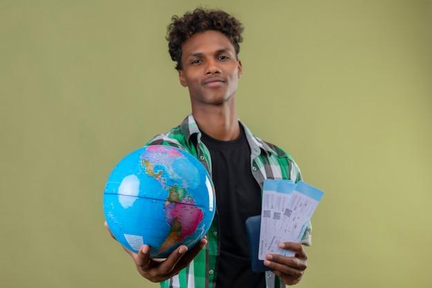 젊은 아프리카 계 미국인 여행자 남자 항공 티켓을 들고 녹색 배경 위에 서있는 자신감을 찾고 카메라에 그것을 뻗어 글로브 무료 사진