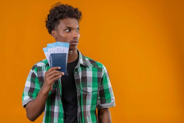 얼굴에 공포 표정으로 제쳐두고 찾고 항공 티켓을 들고 젊은 아프리카 계 미국인 여행자 남자 무료 사진
